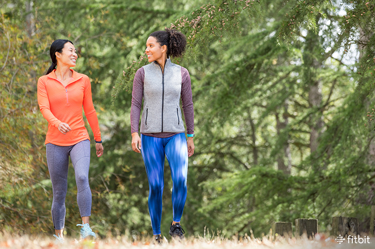 Two women walking while wearing Fitbit trackers.