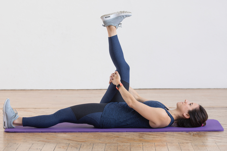 Woman performing a bent-leg pull stretch.